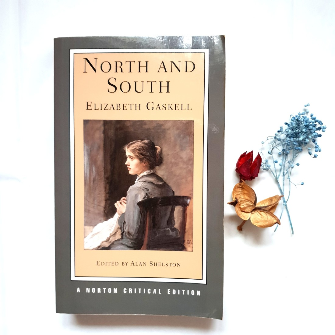 The image depicts a paperback copy of Gaskell's North and South. There are several dried flowers placed in an aesthetically pleasing fashion on the right side of the book